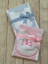 Embroidery is done in a fund kids font, pink thread on pink trim, light blue thread on blue trim.  Pink and Blue Bib and Burp Cloth Set by Wicked Stitches Gifts.