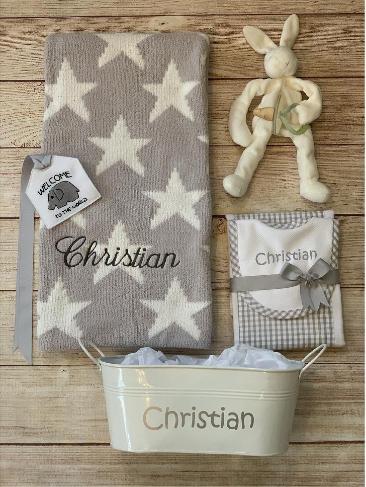 Chenille baby blanket gift by Wicked Stitches Gifts. Shown is the gray stars style with coordinated bib and burp set, binkie buddy, gift tin and tag.