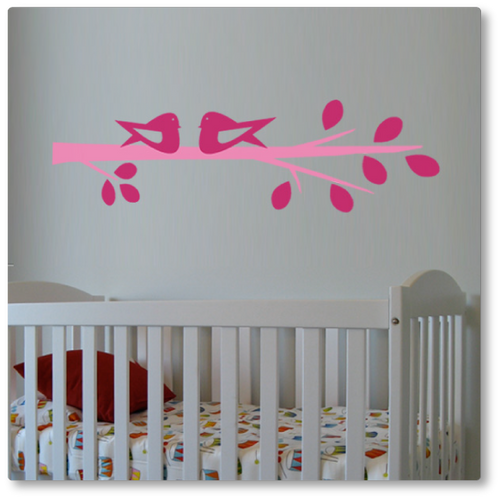 Our cute birds on a branch wall decal features two birds sitting on a branch with leaves. Shown here in pink and light pink on a beige wall.