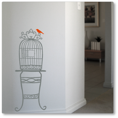 Our quirky birdcage on a table was adapted from a hand drawn image. It adds flair to any wall. Shown in grey, red bird, on a neutral wall.