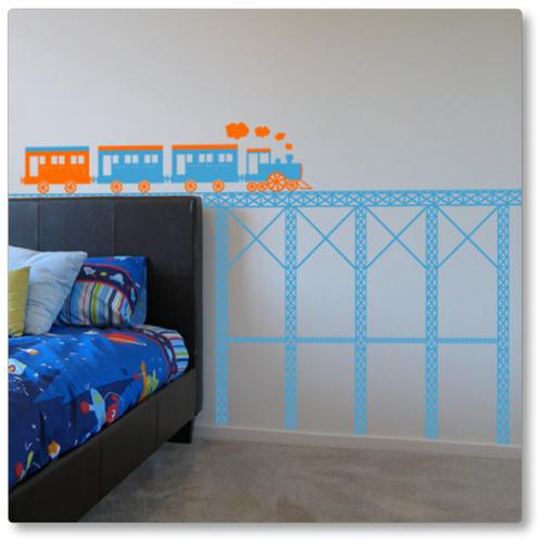 This vinyl decal features a steam train on top of a steel bridge. Shown here in orange and ice blue on a neutral wall.