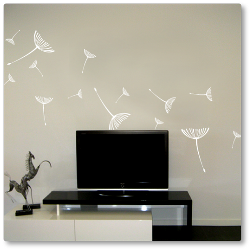 The dandelion seeds flying away decal has fifteen seeds of varying sizes flying away. Shown here in white on a beige wall.