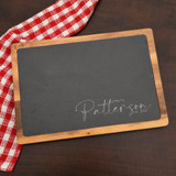 This personalized slate and wood cutting board features the family name and year they were established
