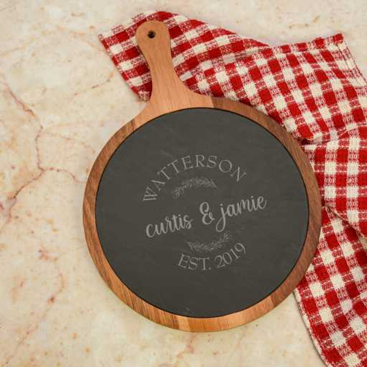Round Acacia wood and slate cutting board with handle is personalized with couple's first names, last name and established year