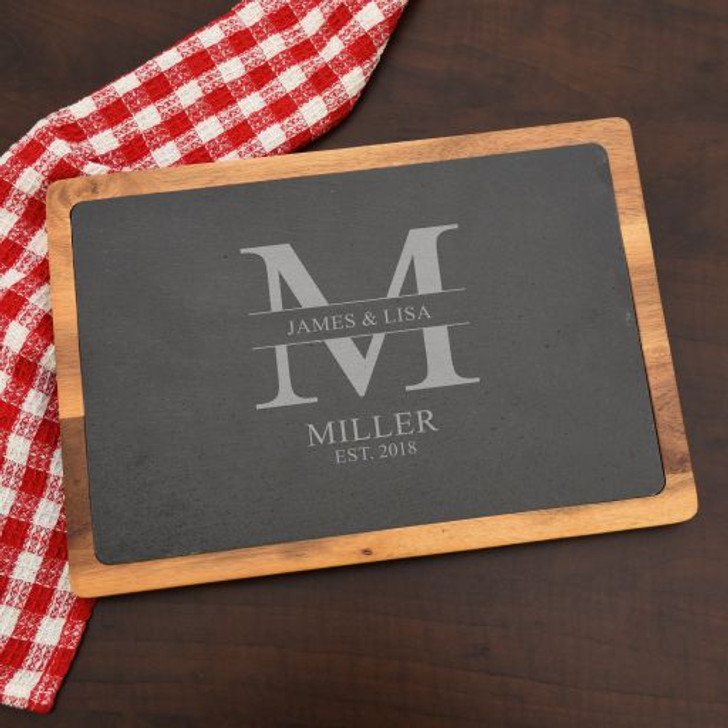 Slate cutting board has a split monogram with couple's first names, last name initial and the year established