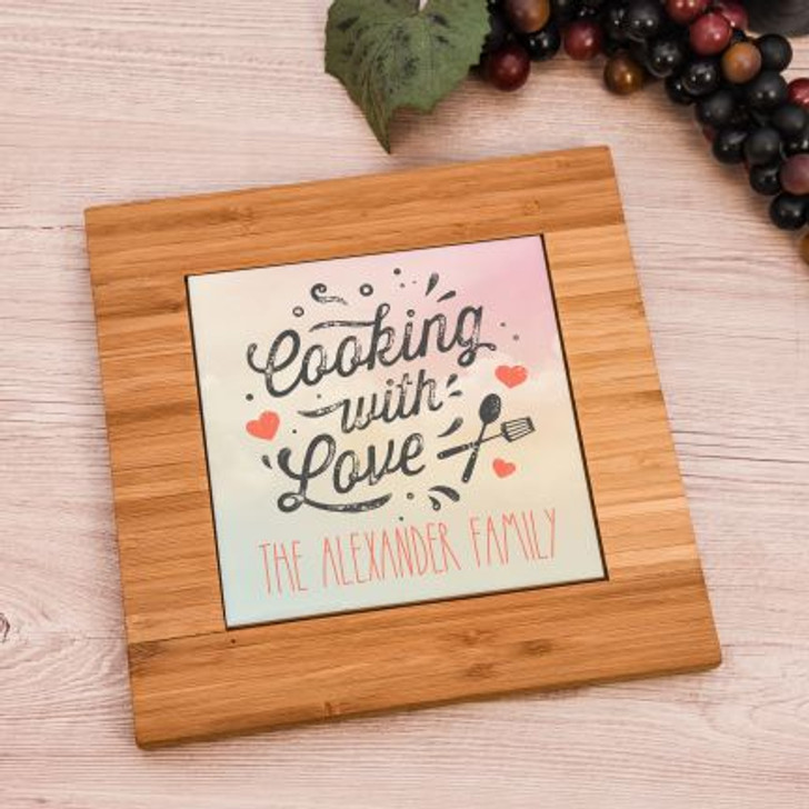 Personalized trivet is made of bamboo with a ceramic insert that has family name