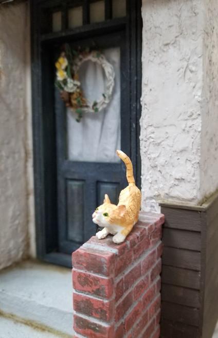Crouching Orange & White Miniature Cat