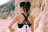 Back view of a woman outside near a cliff wearing a Sierra Designs Women's Tank with Shelf Bra, white, with think outside text