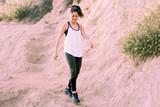 Woman walking outside on a trail wearing Sierra Designs Women's Leggings, olive and black