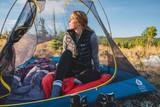 Woman sitting in a Sierra Designs tent with the screen off in a field wearing a Sierra Designs Women's Joshua Vest, olive/gray