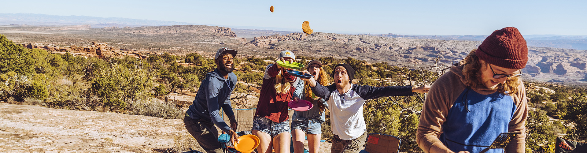 Group of campers trying to catch a flying pancake