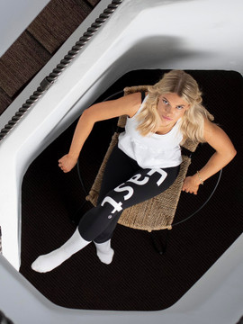 A woman sitting down while wearing Fast leggings.