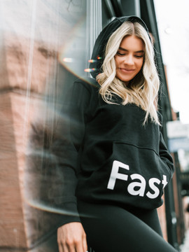 A woman wearing a black Fast-er hoodie.