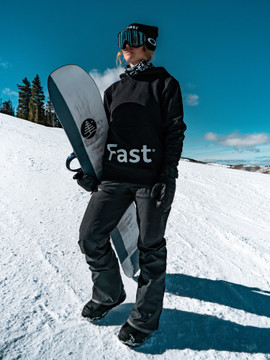 A woman wearing a black Fast-er hoodie while snowboarding.