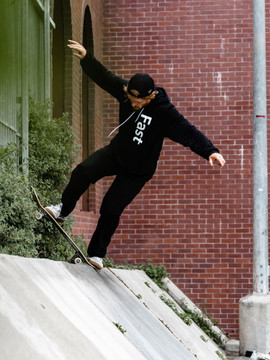 A skateboarder performing a trick while wearing the Vert hoodie by Fast.