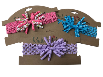 """A stretch crochet band topped with a fun Twiddle Bow is sure to look precious on your little girl. Overall width is approximately 6"""", comfortably stretches to approximately 8"""".  Flower and headband match (or complimentary to patterns in ribbon), unless otherwise requested.  Perfect for newborns through toddlers."""