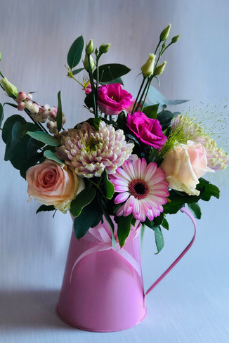 A beautiful mix of pretty pink seasonal flowers in a keepsake jug!