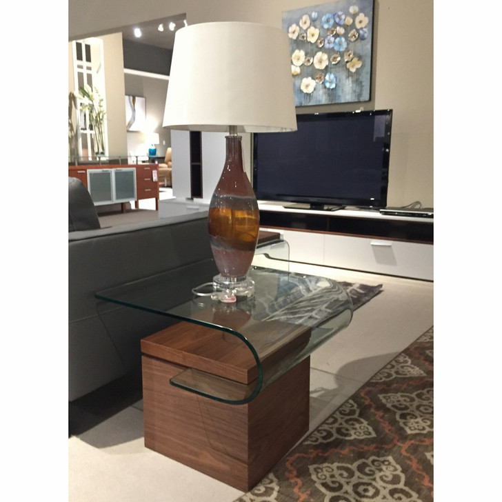 end table constructed out of dark wood base and curved glass top. The table is styled with a brown glass lamp