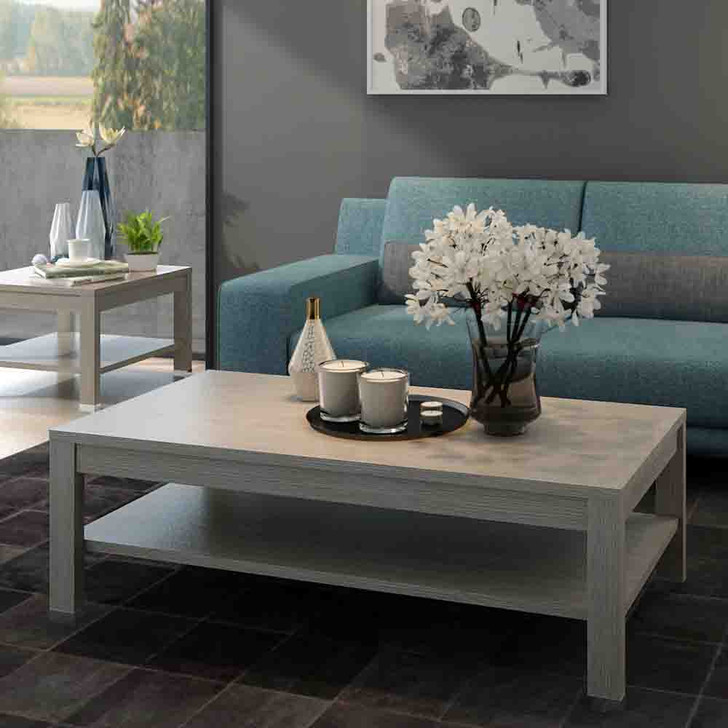 Simple coffee table in grey melamine with a bi-level design. Features decorative elements on top including an empty vase, two candles, and a vase of flowers.