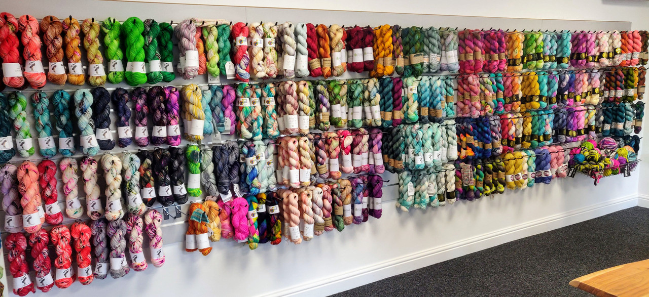 A long section of slatwall filled with hundreds of skeins of hand-dyed yarn, mostly 4ply, from a range of UK indie-dyers