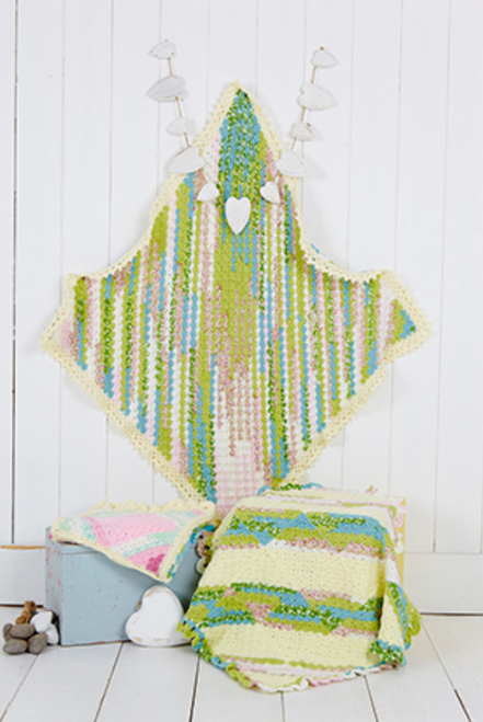 A green variegated crocheted blanket is hung up on a wall with another green variegated one folded up next to it.