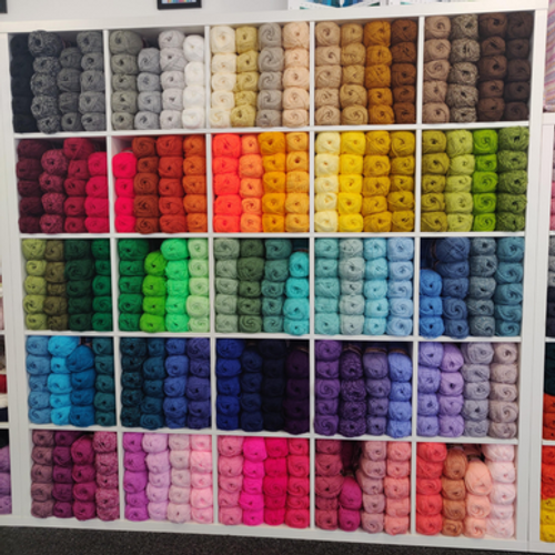 A 5x5 cube shelving unit showing all 100 shades of Stylecraft Special DK.