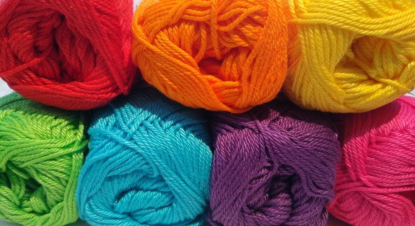 Seven 50g balls of cotton in rainbow colours.