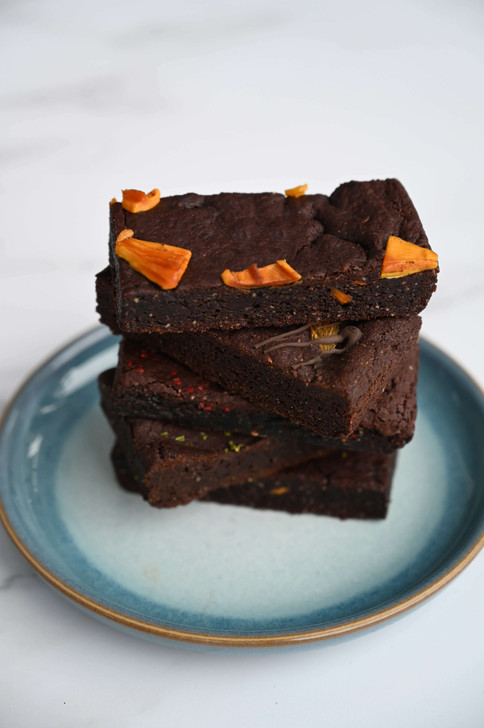 Stack of four mango and ginger brownie slices on blue plate