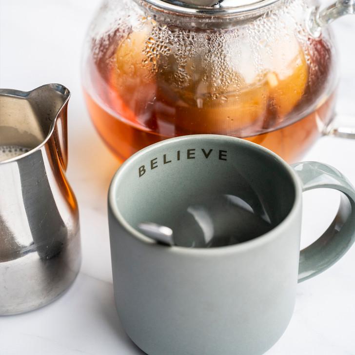 """Believe"" Handmade dark grey ceramic mug alongside a glass tea pot and vegan milk pot"