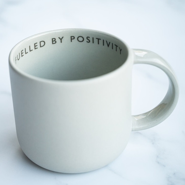 "Light grey handmade ceramic mug printed with ""fuelled by positivity"" quote"