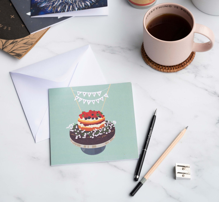 Happy Birthday card with pen and pencil and mug of coffee