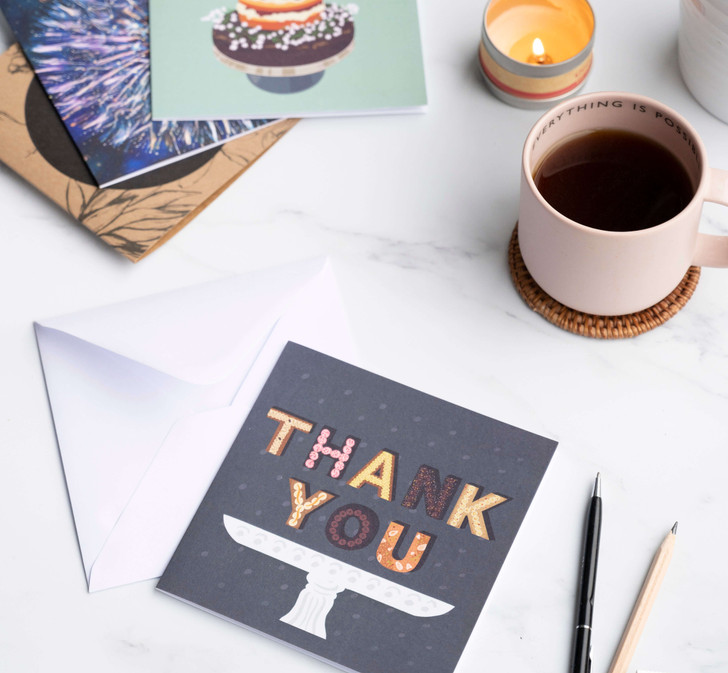 Thank you greeting card with pen and pencil and mug of coffee