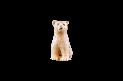"This is a beautiful hand carved eco-ivory Bear Sitting Statue.  The dimensions of the Bear Sitting Statue are .64"" x 1.38"" x .91"".  The SKU is C-15.  This unique Bear Sitting statue will make a great addition to any room in the house.  You can place it on any flat surface to diplay, or a great gift for children to have.  All statues are hand carved in clay.  We then make a mold of the original piece before producing them into the final acrylic resin product."