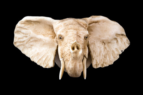 """This is a stunning hand carved eco-ivory Elephant plaque, that has the Elephant's trunk Up. The dimensions of the elephant plaque are 5.36"""" x 3.60"""" x 4.35"""". The SKU is C-1.  This unique Elephant plaque will make a great addition to any room in the house. You can hang it up to display on walls, or remove the plaque backing to have the Elephant shown on a flat surface.  This piece was originally hand carved by Sheryl Tray, an artist located in Hawaii. The artwork you see here is a memory, captured in clay by Sheryl in her many travels. The clay original, sculpted in her small studio in Honolulu, is sent to a sent to us to be cast in either metal or resin and presented here for you to enjoy. Please take a piece home for yourself, or as a present for a special friend who loves and values the great outdoors as much as Sheryl."""