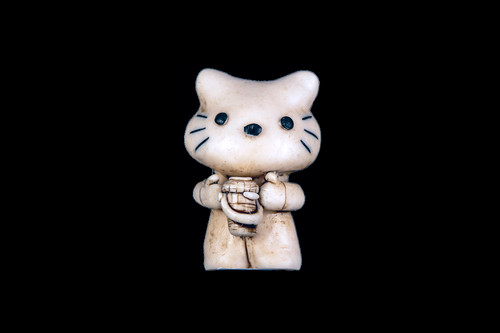 """This is a stunning hand carved eco-ivory Cat Statue. The dimensions of the Cat Statue are 1.41"""" x 2.47"""" x 1.51"""". This beatuiful design has a carved Cat holding a Nantucket Basket. The SKU is C-65.  This unique Double Cat Statue will make a great addition to any room in the house. You can place it on any flat surface to display, or a great gift for children to have.  This piece was originally hand carved by Sheryl Tray, an artist located in Hawaii. The artwork you see here is a memory, captured in clay by Sheryl in her many travels. The clay original, sculpted in her small studio in Honolulu, is sent to a sent to us to be cast in either metal or resin and presented here for you to enjoy. Please take a piece home for yourself, or as a present for a special friend who loves and values the great outdoors as much as Sheryl."""
