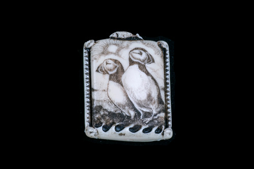 """This is a beautiful originally hand etched Puffin designed pin/pendant. The backing of this piece has the findings to be a pin, as well as a pendant. They come with an 18"""" Silver Plated Chain. This is part of the incredible line of Mossup Valley Designs that we carry, with the wonderful artist Rachel Badeau. The dimensions of the necklace are 1.21"""" x 1.57"""" x 0.35"""". The SKU is MVD PN 14.  Rachel Badeau has been etching and engraving in a variety of media for over thirty years. Her work, characterized by fine line and intricate detail, attempts to touch the hearts and emotions of others. All while reflecting her love of animals, nature and the human spirit.  The resin scrimshaw piece is originally hand etched by Rachel Badeau. We make a mold of the original piece and do an open cast pour of our resin mixture. The pieces are removed from the mold and sanded and inked."""