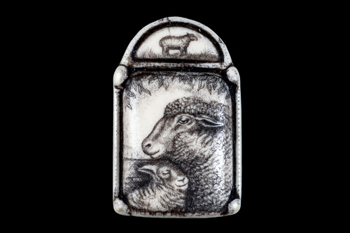 """This is a beautiful originally hand etched Ewe and Lamb designed pin/pendant. The backing of this piece has the findings to be a pin, as well as a pendant. They come with an 18"""" Silver Plated Chain. This is part of the incredible line of Mossup Valley Designs that we carry, with the wonderful artist Rachel Badeau. The dimensions of the necklace are 1.26"""" x 1.96"""" x 0.33"""". The SKU is MVD PN 17.  Rachel Badeau has been etching and engraving in a variety of media for over thirty years. Her work, characterized by fine line and intricate detail, attempts to touch the hearts and emotions of others. All while reflecting her love of animals, nature and the human spirit.  The resin scrimshaw piece is originally hand etched by Rachel Badeau. We make a mold of the original piece and do an open cast pour of our resin mixture. The pieces are removed from the mold and sanded and inked."""