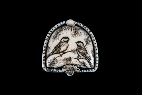"This is a beautiful originally hand etched Chickadees designed pin/pendant. The backing of this piece has the findings to be a pin, as well as a pendant.  They come with an 18"" Silver Plated Chain.  This is part of the incredible line of Mossup Valley Designs that we carry, with the wonderful artist Rachel Badeau.  The dimensions of the necklace are 1.36"" x 1.36"" x 0.34"".  The SKU is MVD PN 24.  Rachel Badeau has been etching and engraving in a variety of media for over thirty years.  Her work, characterized by fine line and intricate detail, attempts to touch the hearts and emotions of others.  All while reflecting her love of animals, nature and the human spirit.    The resin scrimshaw piece is originally hand etched by Rachel Badeau.  We make a mold of the original piece and do an open cast pour of our resin mixture.  The pieces are removed from the mold and sanded and inked."