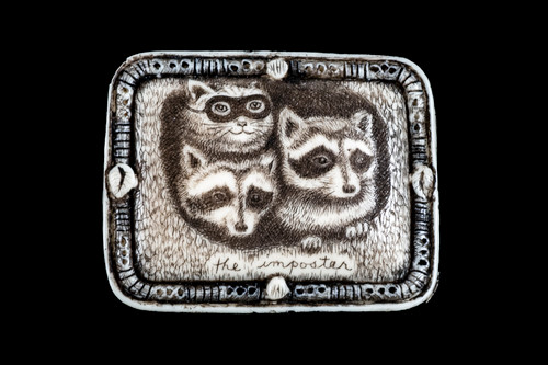 """This unique originally hand etched The Imposter designed pin/pendant. The design has a disguised cat mixed in with raccoons. The backing of this piece has the findings to be a pin, as well as a pendant. They come with an 18"""" Silver Plated Chain. This is part of the incredible line of Mossup Valley Designs that we carry, with the wonderful artist Rachel Badeau. The dimensions of the necklace are 1.82"""" x 1.42"""" x 0.36"""". The SKU is MVD PN 19.  Rachel Badeau has been etching and engraving in a variety of media for over thirty years. Her work, characterized by fine line and intricate detail, attempts to touch the hearts and emotions of others. All while reflecting her love of animals, nature and the human spirit.  The resin scrimshaw piece is originally hand etched by Rachel Badeau. We make a mold of the original piece and do an open cast pour of our resin mixture. The pieces are removed from the mold and sanded and inked."""