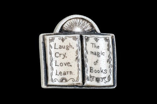 """This distinct originally hand etched Magic of Books designed pin/pendant. The design has a book shaped Pin/Pendant, with the saying """"Laugh, Cry, Love, Learn. The Magic of Books"""". The backing of this piece has the findings to be a pin, as well as a pendant. They come with an 18"""" Silver Plated Chain. This is part of the incredible line of Mossup Valley Designs that we carry, with the wonderful artist Rachel Badeau. The dimensions of the necklace are 1.33"""" x 1.29"""" x 0.37"""". The SKU is MVD PN 21.  Rachel Badeau has been etching and engraving in a variety of media for over thirty years. Her work, characterized by fine line and intricate detail, attempts to touch the hearts and emotions of others. All while reflecting her love of animals, nature and the human spirit.  The resin scrimshaw piece is originally hand etched by Rachel Badeau. We make a mold of the original piece and do an open cast pour of our resin mixture. The pieces are removed from the mold and sanded and inked."""