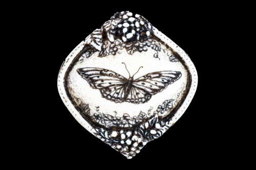 """This distinct originally hand etched Free Flight designed pin/pendant. The Free Flight design is that of a butterfly. The backing of this piece has the findings to be a pin, as well as a pendant. They come with an 18"""" Silver Plated Chain. This is part of the incredible line of Mossup Valley Designs that we carry, with the wonderful artist Rachel Badeau. The dimensions of the necklace are 1.51"""" x 1.61"""" x 0.37"""". The SKU is MVD PN 34.  Rachel Badeau has been etching and engraving in a variety of media for over thirty years. Her work, characterized by fine line and intricate detail, attempts to touch the hearts and emotions of others. All while reflecting her love of animals, nature and the human spirit.  The resin scrimshaw piece is originally hand etched by Rachel Badeau. We make a mold of the original piece and do an open cast pour of our resin mixture. The pieces are removed from the mold and sanded and inked."""