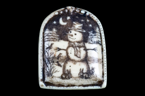 """This distinct originally hand etched Winter Night designed pin/pendant. The Winter Night design is that of a Snowman. The backing of this piece has the findings to be a pin, as well as a pendant. They come with an 18"""" Silver Plated Chain. This is part of the incredible line of Mossup Valley Designs that we carry, with the wonderful artist Rachel Badeau. The dimensions of the necklace are 1.17"""" x 1.44"""" x 0.37"""". The SKU is MVD PN 37.  Rachel Badeau has been etching and engraving in a variety of media for over thirty years. Her work, characterized by fine line and intricate detail, attempts to touch the hearts and emotions of others. All while reflecting her love of animals, nature and the human spirit.  The resin scrimshaw piece is originally hand etched by Rachel Badeau. We make a mold of the original piece and do an open cast pour of our resin mixture. The pieces are removed from the mold and sanded and inked."""