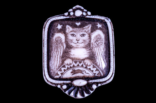 """This distinct originally hand etched Angel Cat designed pin/pendant. The Angel Cat design features a cat and a mouse. The backing of this piece has the findings to be a pin, as well as a pendant. They come with an 18"""" Silver Plated Chain. This is part of the incredible line of Mossup Valley Designs that we carry, with the wonderful artist Rachel Badeau. The dimensions of the necklace are 1.26"""" x 1.71"""" x 0.43"""". The SKU is MVD PN 4.  Rachel Badeau has been etching and engraving in a variety of media for over thirty years. Her work, characterized by fine line and intricate detail, attempts to touch the hearts and emotions of others. All while reflecting her love of animals, nature and the human spirit.  The resin scrimshaw piece is originally hand etched by Rachel Badeau. We make a mold of the original piece and do an open cast pour of our resin mixture. The pieces are removed from the mold and sanded and inked."""