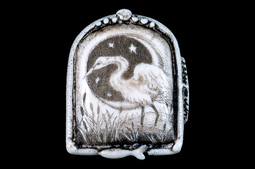 """This distinct originally hand etched Great Egret designed pin/pendant. They come with an 18"""" Silver Plated Chain. This is part of the incredible line of Mossup Valley Designs that we carry, with the wonderful artist Rachel Badeau. The dimensions of the necklace are 1.23 x 1.51"""" x 0.37"""". The SKU is MVD PN 47.  Rachel Badeau has been etching and engraving in a variety of media for over thirty years. Her work, characterized by fine line and intricate detail, attempts to touch the hearts and emotions of others. All while reflecting her love of animals, nature and the human spirit.  The resin scrimshaw piece is originally hand etched by Rachel Badeau. We make a mold of the original piece and do an open cast pour of our resin mixture. The pieces are removed from the mold and sanded and inked."""