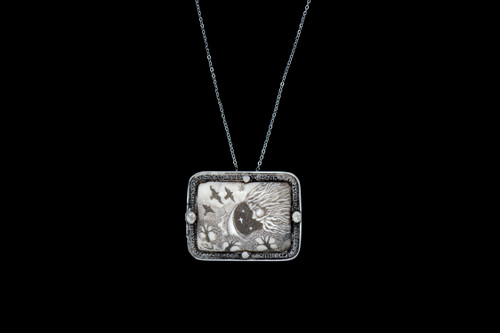 """MVD PN 49 North Wind Necklace.  This distinct originally hand etched North Wind designed pin/pendant. They come with an 18"""" Silver Plated Chain. This is part of the incredible line of Mossup Valley Designs that we carry, with the wonderful artist Rachel Badeau. The dimensions of the necklace are 1.80"""" x 1.41"""" x 0.37"""". The SKU is MVD PN 48.  Rachel Badeau has been etching and engraving in a variety of media for over thirty years. Her work, characterized by fine line and intricate detail, attempts to touch the hearts and emotions of others. All while reflecting her love of animals, nature and the human spirit.  The resin scrimshaw piece is originally hand etched by Rachel Badeau. We make a mold of the original piece and do an open cast pour of our resin mixture. The pieces are removed from the mold and sanded and inked."""
