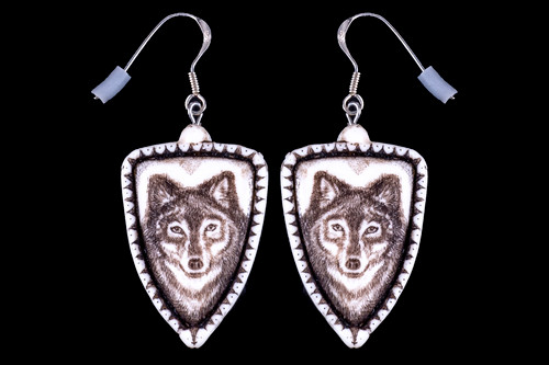 "This is a beautiful originally hand etched Wolf French Wire Earring set. This is part of the incredible line of Mossup Valley Designs that we carry, with the wonderful artist Rachel Badeau.  All the earrings come carded.  The dimensions of the earrings are .90"" x 1.36"" x 0.18"".  The SKU is MVD ER 01.  Rachel Badeau has been etching and engraving in a variety of media for over thirty years.  Her work, characterized by fine line and intricate detail, attempts to touch the hearts and emotions of others.  All while reflecting her love of animals, nature and the human spirit.    The resin scrimshaw piece is originally hand etched by Rachel Badeau.  We make a mold of the original piece and do an open cast pour of our resin mixture.  The pieces are removed from the mold and sanded and inked."
