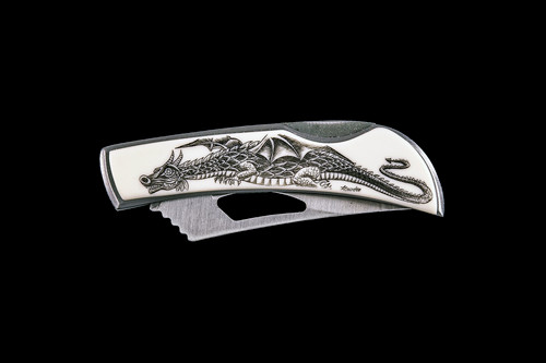 """This unique originally hand etched Dragon design on a Stainless Steel Silver Hawk Knife. The back of the knife has a belt clip and all the knifes come with the pictured sheath. It is a lock blade knife and a useful pocket knife. The artwork was originally hand etched by Linda Layden. The dimensions of the Silver Hawk knife with the blade closed are 3.00"""" x 0.96"""" x 0.55"""". The blade itself is approximately 2.35"""" making the width of the knife with an open blade 5.35"""". The SKU is NC 14 - 500.  Linda Layden has been making beautiful works of art in the scrimshaw field for over 40 years. Originally a hobby that became a full time job. Her work can be found in gift shops, galleries and museums across the world."""