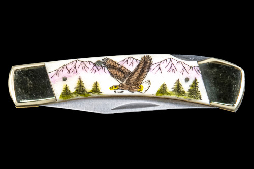 "This unique hand etched Colored Soaring Eagle design on a 440 Stainless Steel Blade LB 5 Knife.  This beautiful knife is part of the Scrimshaw Collection, with those words laser engraved into the blade.  The LB 5 knifes come with the pictured leather sheath and each scale is made with Bovine Bone.  The LB 5 Knife has bolsters and shackle that are nickel silver with brass pins and liner.  It is a lock blade knife and a very useful pocket knife. The dimensions of the LB 5 Pocket Knife with the blade closed are 3.71"" x 0.90"" x 0.39"".  The blade itself is approximately 2.80"" making the width of the knife with an open blade 6.51"".  The SKU is LB-5 113.  The scrimshaw is inked with colored india ink and sealed with renaissance wax, which is used by museums for antique restoration.  It also helps bring out the beauty of the artwork as well as in the cow bone. The knife is water resistant, but not waterproof."