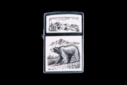 """This is a beautiful originally hand etched Eco-Ivory Scrimshaw Bear designed Zippo Lighter! The top of the flip lighter has a a Mountain Skyline Top piece. The Zippo is a Brushed Chrome finish. Each lighter has a bottom stamp signifying the year it was made, is refillable. All windproof lighters are American made in Bradford, PA factory and come packaged in a gift box. This is part of the Save the Elephant Collection and was originally hand etched by Linda Layden. The SKU is NC 54 - 131.  The Zippo Lighter is 2.24"""" x 1.51"""" x 0.59"""". It weighs 2.04 oz."""