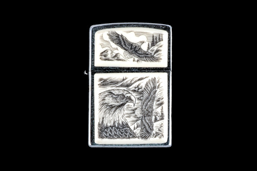 """This is a unique originally hand etched Eco-Ivory Scrimshaw Eagle Face with Soaring Eagle designed Zippo Lighter! The top of the flip lighter has a a Soaring Eagle Top piece. The Zippo is a Brushed Chrome finish. Each lighter has a bottom stamp signifying the year it was made, is refillable. All windproof lighters are American made in Bradford, PA factory and come packaged in a gift box. This is part of the Save the Elephant Collection and was originally hand etched by Linda Layden. The SKU is NC 54 - 142  The Zippo Lighter is 2.24"""" x 1.51"""" x 0.59"""". It weighs 2.04 oz."""